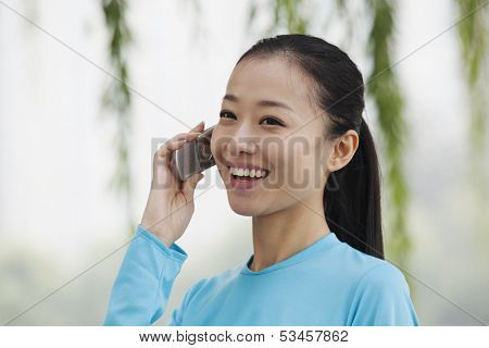 Young woman talking on cell phone in park