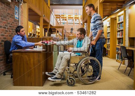 Side view of a male student in wheelchair at the counter in college library