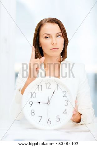 business, office, time management, deadline, school and education concept - attractive businesswoman showing clock