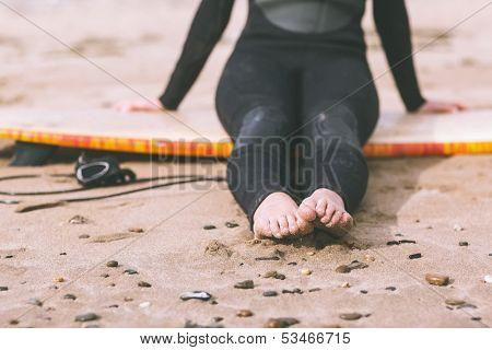 Low section of a young woman in wet suit with surfboard sitting at the beach