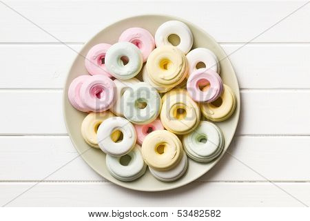 top view of colorful meringues on plate on white wooden table