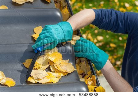 Man Cleaning The Roof In Autumn