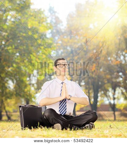 Young businessperson with eyeglasses doing yoga exercise seated on a green grass in a park, shot with a tilt and shift lens
