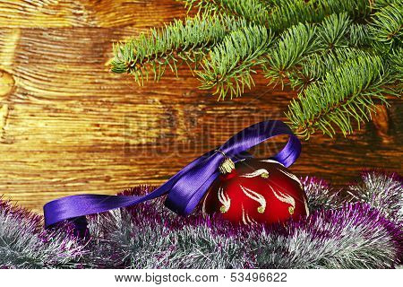 Christmas Decoration. Red Ball With Violet Ribbon, Fir-tree And Tinsel. Selective Focus