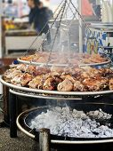image of brazier  - roasted pork knuckle on large brazier in country fair - JPG