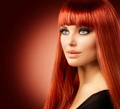 Beauty Woman Portrait. Red Hair Model Girl Face. Sexy Woman with Long Shiny Straight Red Hair Isolat