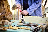 stock photo of workbench  - Carpenter working and chiseling by hand in his old wooden workbench - JPG