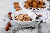 stock photo of toffee  - Many toffee on plate and in bowl on napkin on board on wooden table - JPG