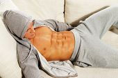 stock photo of hoodie  - Sporty man in grey hoodie with muscular torso relaxing on sofa - JPG