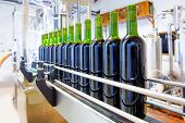 foto of humidity  - red wine in glass bottling machine at winery - JPG