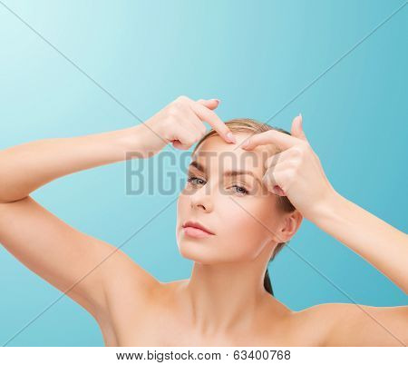 health and beauty concept - face of beautiful young woman squeezing acne spots