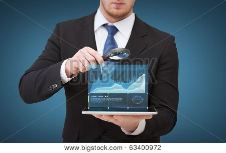 technology, internet and business concept - businessman holding magnifying glass over tablet pc computer with growing chart
