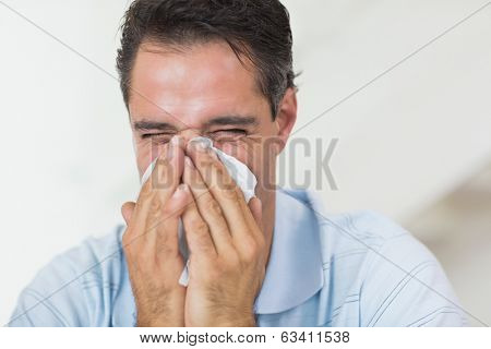 Closeup of a man suffering from cold with eyes closed