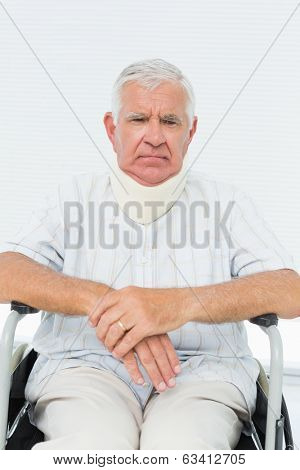 Portrait of a sad senior man sitting in wheelchair with cervical collar at the medical office