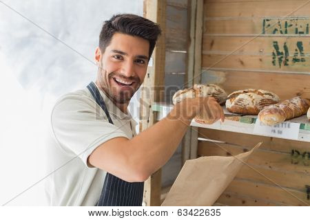 Portrait of confident male cafe owner with sweet food at coffee shop