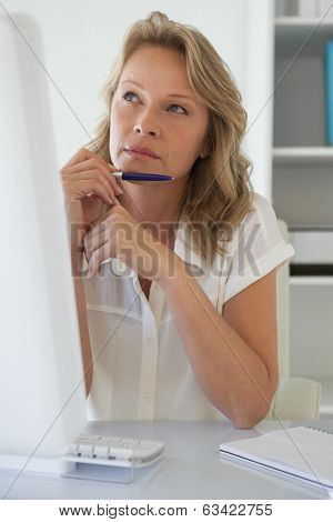 Casual businesswoman thinking at her desk in her office