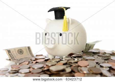 A white piggy bank wearing a graduation cap, sitting on a heap of bills and change -- signifying the expense of college or new hopes for earnings.  On a white background.