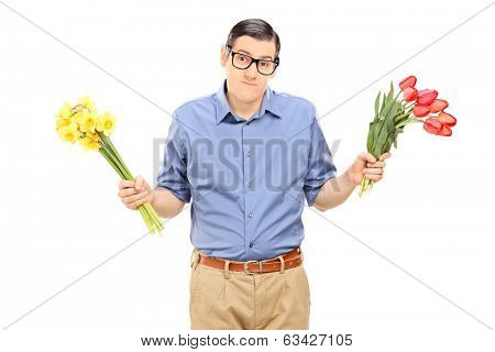 Indecisive man holding red and yellow tulips isolated on white background