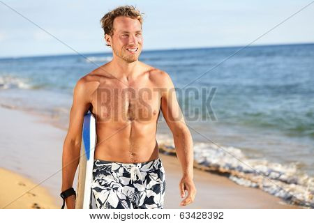 Surfer fun on summer beach - handsome man. Bodyboarding surfing good looking fit fitness model running with bodyboard surfboard during vacation holidays getaway. Caucasian male model in his 20s.