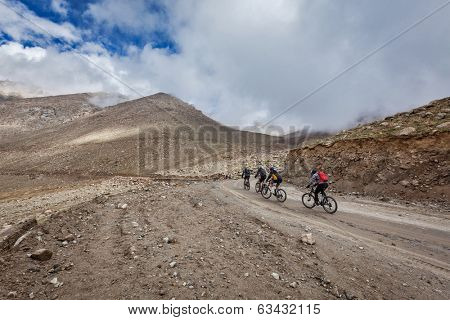KARDUNG LA PASS, INDIA - SEPTEMBER 5, 2011: Bicycle tourists in Himalayas ascend Khardung La - highest motorable pass in the world. Himalayan bicycle tourism is gaining popularity all over the world