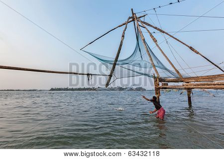 KOCHI, INDIA - FEBRUARY 25, 2013: Local fisherman fishing with net near Kochi chinese fishnets. Fort Kochin, Kochi, Kerala, India