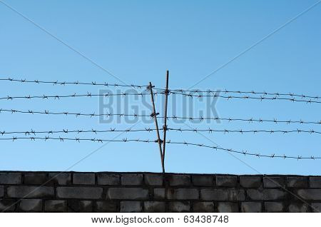 Barbed Wire Stretched Over Brick Wall
