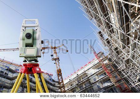 surveyors measuring instrument, close-ups, large super-wide construction site in background