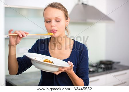 Pretty, young woman cooking a diner in a modern kitchen, tasing the food she made