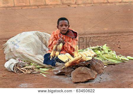 African Boy Sells Corn Grill.