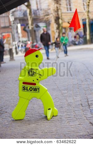 Plastic Man Slow Road Sign Holding Red Flag