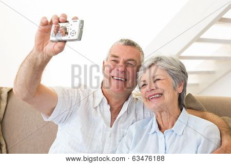Senior couple sitting on couch taking a selfie at home in living room