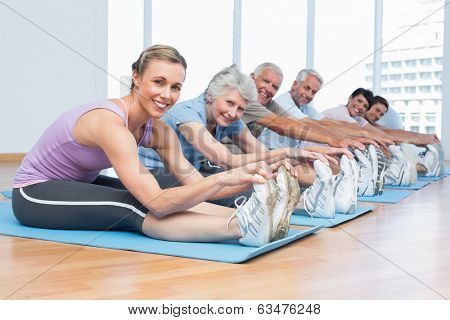 Happy female trainer with class stretching hands to legs at yoga class