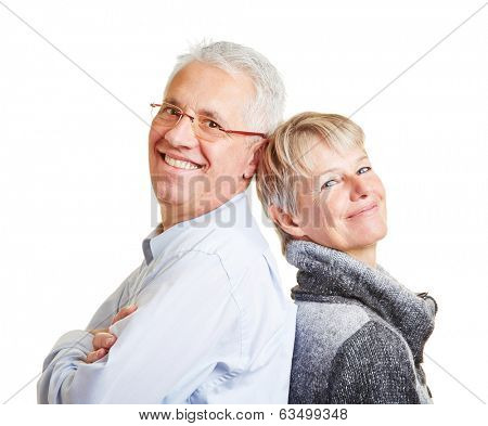 Happy senior couple leaning on each other back to back