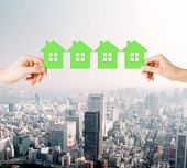 real estate and family home concept - closeup picture of male and female hands holding many green pa