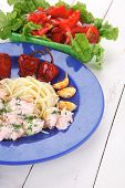 fresh rose wild salmon baked in cream cheese sauce with italian pasta and red hot pepper on blue pla