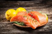 stock photo of wood pieces  - Fresh salmon with herbs and lemon on wood - JPG
