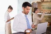 Businessman using mobile phone and laptop with colleagues behind in office cafeteria