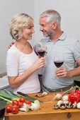 Loving mature couple with wine glasses in the kitchen at home