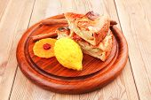baked food : apple pie triangles served with lemon and cinnamon on wood table