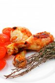 grilled chicken drumstick with tomatoes and thyme on white plate isolated over white background