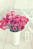 Vintage shabby chic photo of bouquet of spring tulips in a old tin vase on white wooden floor