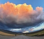 Huge pink - orange cloud, like a bowl of cream, lit the last rays of sunset. Gravel road through the