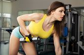 image of crossed legs  - Young slim woman exercising in a gym - JPG