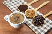 coffee beans and sugar in wooden spoon with cup of coffee