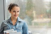 Smiling student with books in front of wet window