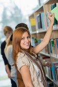 Student taking book from bookshelf with classmates in school library