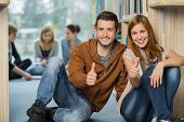 Happy university students showing thumb up with friends in library