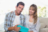 Loving young couple with gift box sitting on sofa at home