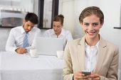 Businesswoman text messaging with colleagues in meeting behind at office desk