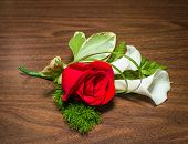 picture of boutonniere  - Beautiful boutonniere with rose and callas on a table.